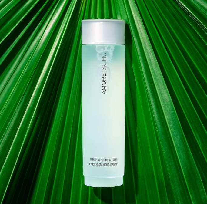 A bottle of the botanical soothing toner laying on top of green foliage