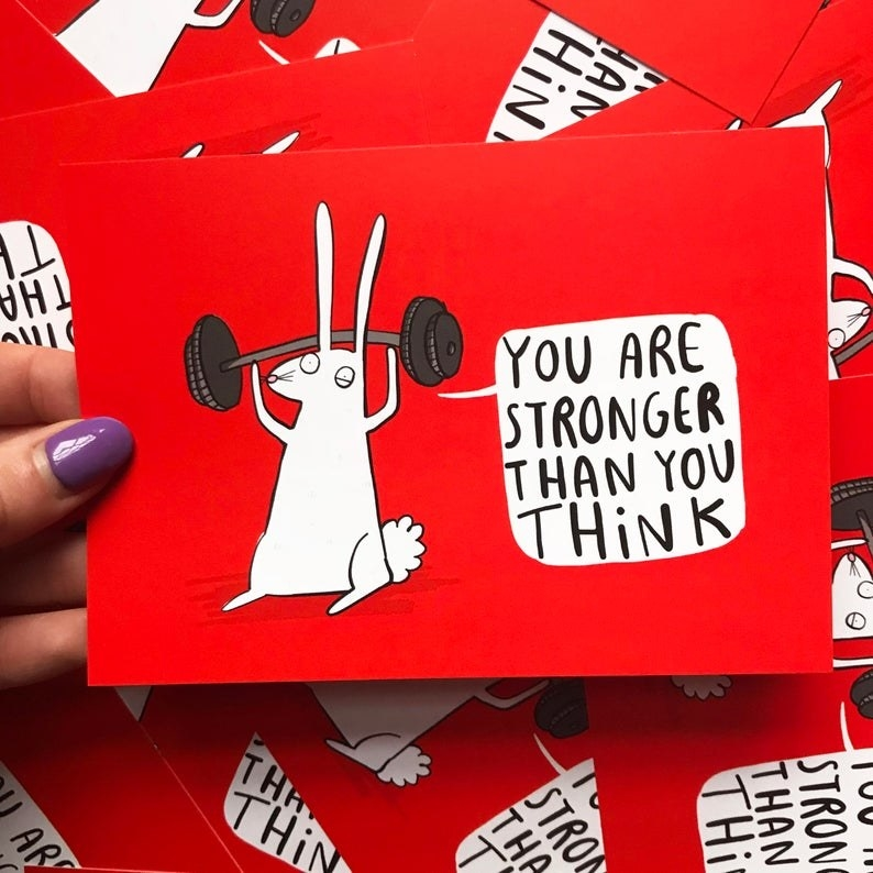 "The red card featuring a drawing of a bunny lifting a dumbbell and the text ""You are stronger than you think"""