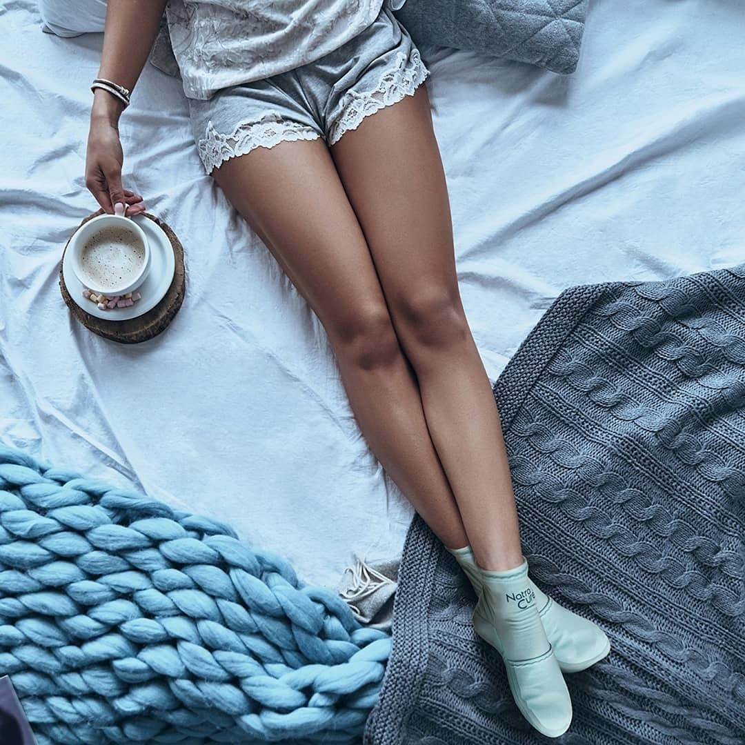 A person wearing cold therapy  socks on their bed while drinking a latte