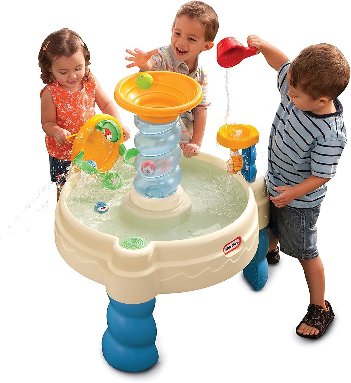 Three kids standing around a play table full of water
