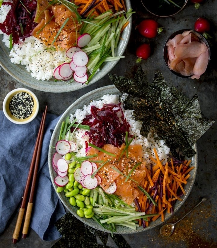 Two salmon sushi bowls with cucumbers, carrots, beets, radishes, and edamame over white rice.