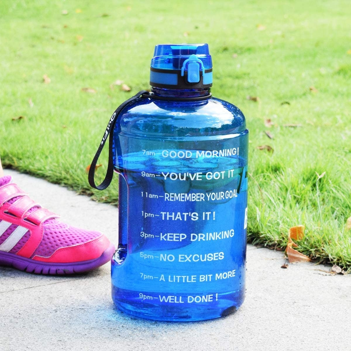 A time-marked waterbottle on the pavement beside a lawn and someone's foot