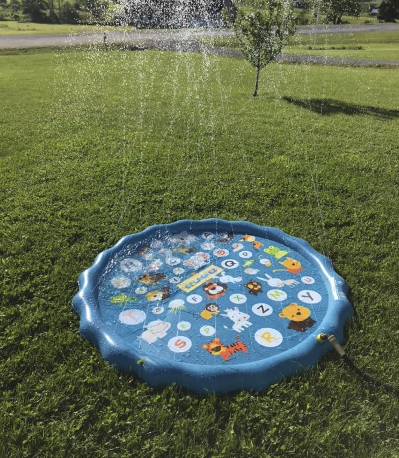 Reviewer pic of the small inflatable pool with water shooting up from the squirters all around the outside