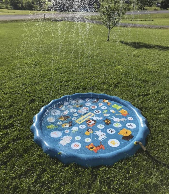 A small inflatable pool with water shooting up from the squirters all around the rim of it. It's sitting in a yard, attached to a hose.