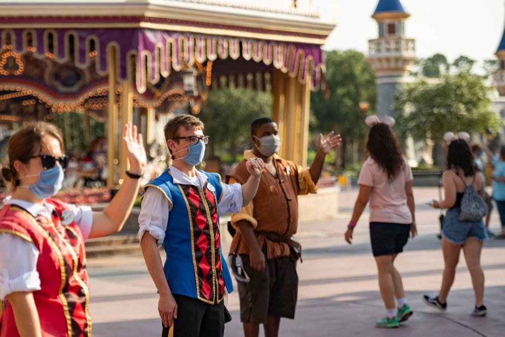 Disney cast member greet visitors while wearing protective masks