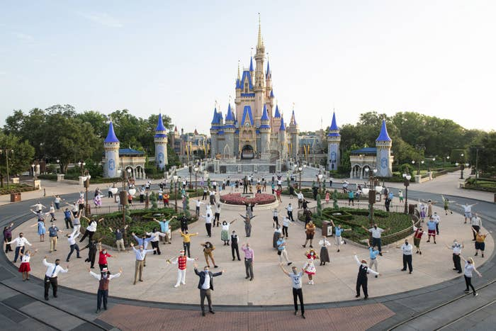 Disney World employees pose while socially distanced outside Cinderella's Castle