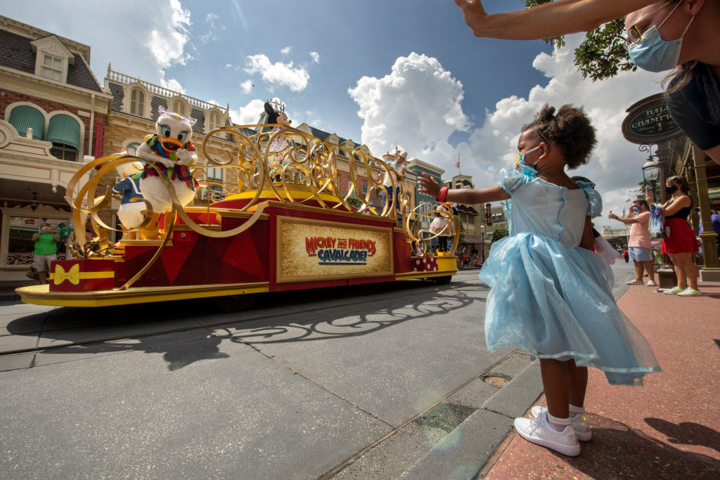 A little girl in a Cinderella dress and a mask waves to Daisy Duck during the cavalcade