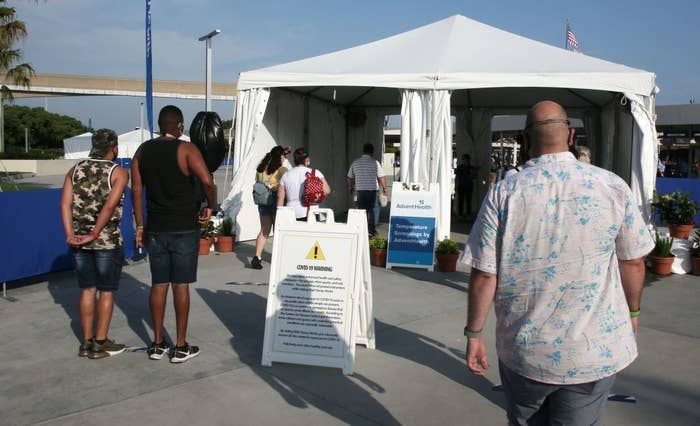 Visitors walk toward a tent to get their temperatures checked before entering the park