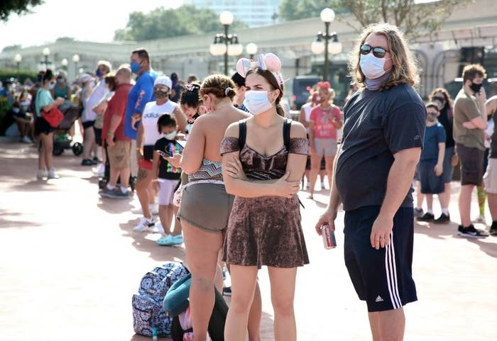 A crowd of people wearing  masks waits to enter the park