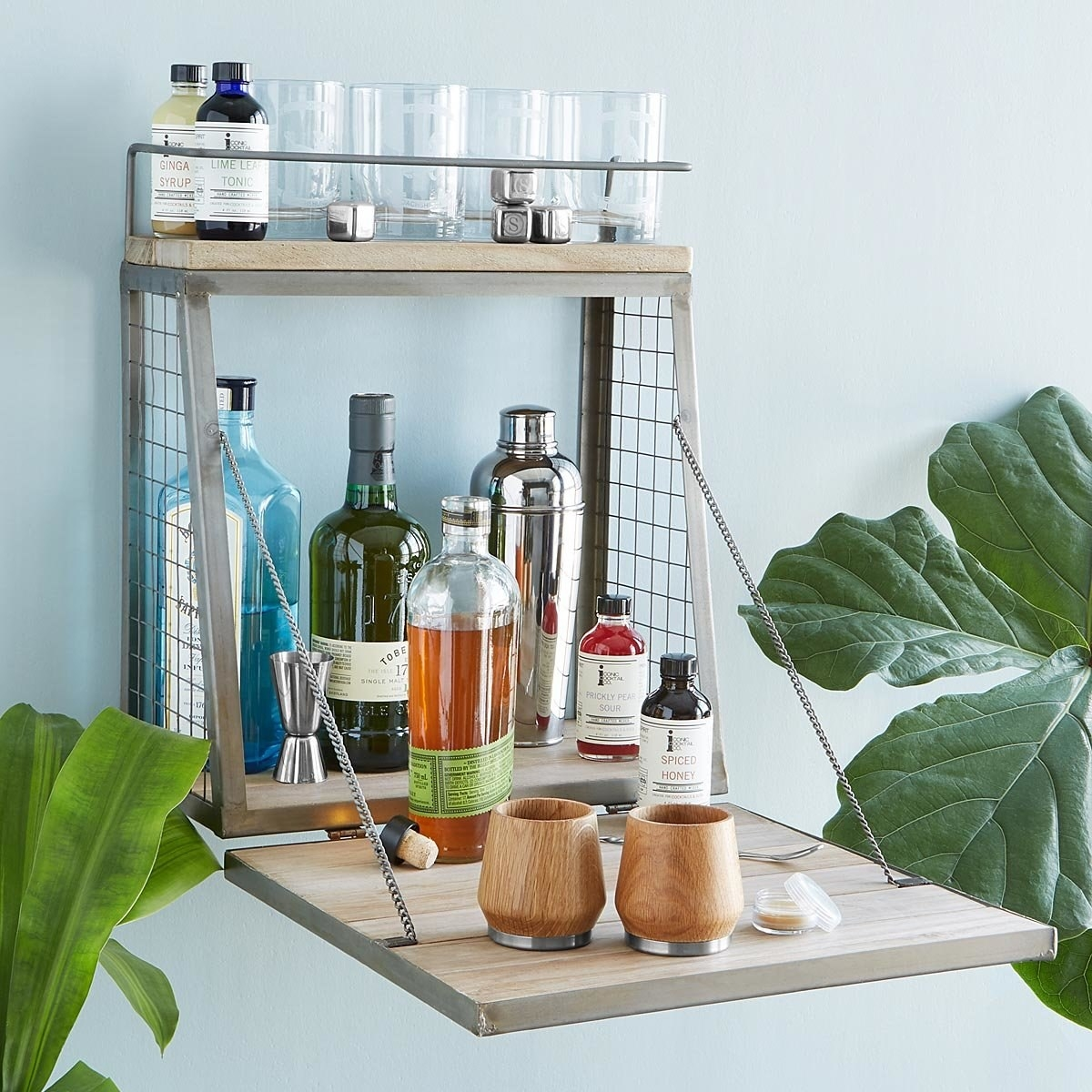 The wall-mounted fold-down shelf loaded with alcohol bottles and glasses