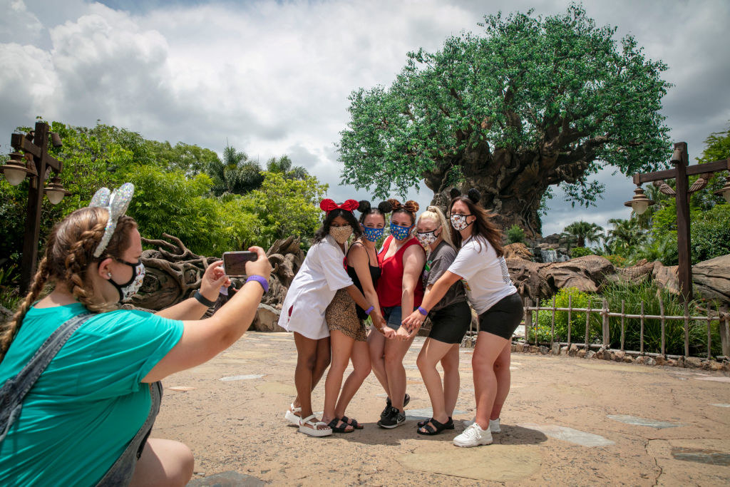A group of girls in Mick Mouse ears and face masks pose in the Animal Kingdom theme park