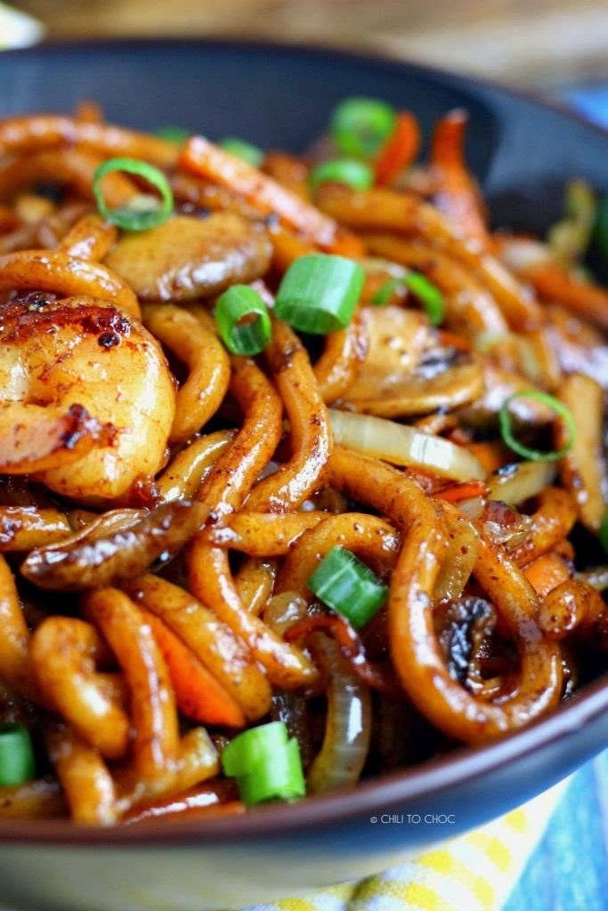 A bowl of udon noodle stir fry with carrots, mushrooms, and scallions tossed in soy sauce.