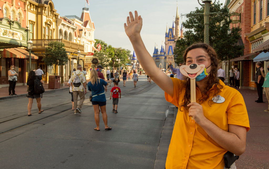 A worker holds a Mickey Mouse smile sign over her face mask