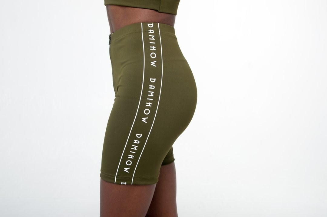 "The high-waisted biker shorts in green  with a white stripe down the side with ""Damihow"" written three times"