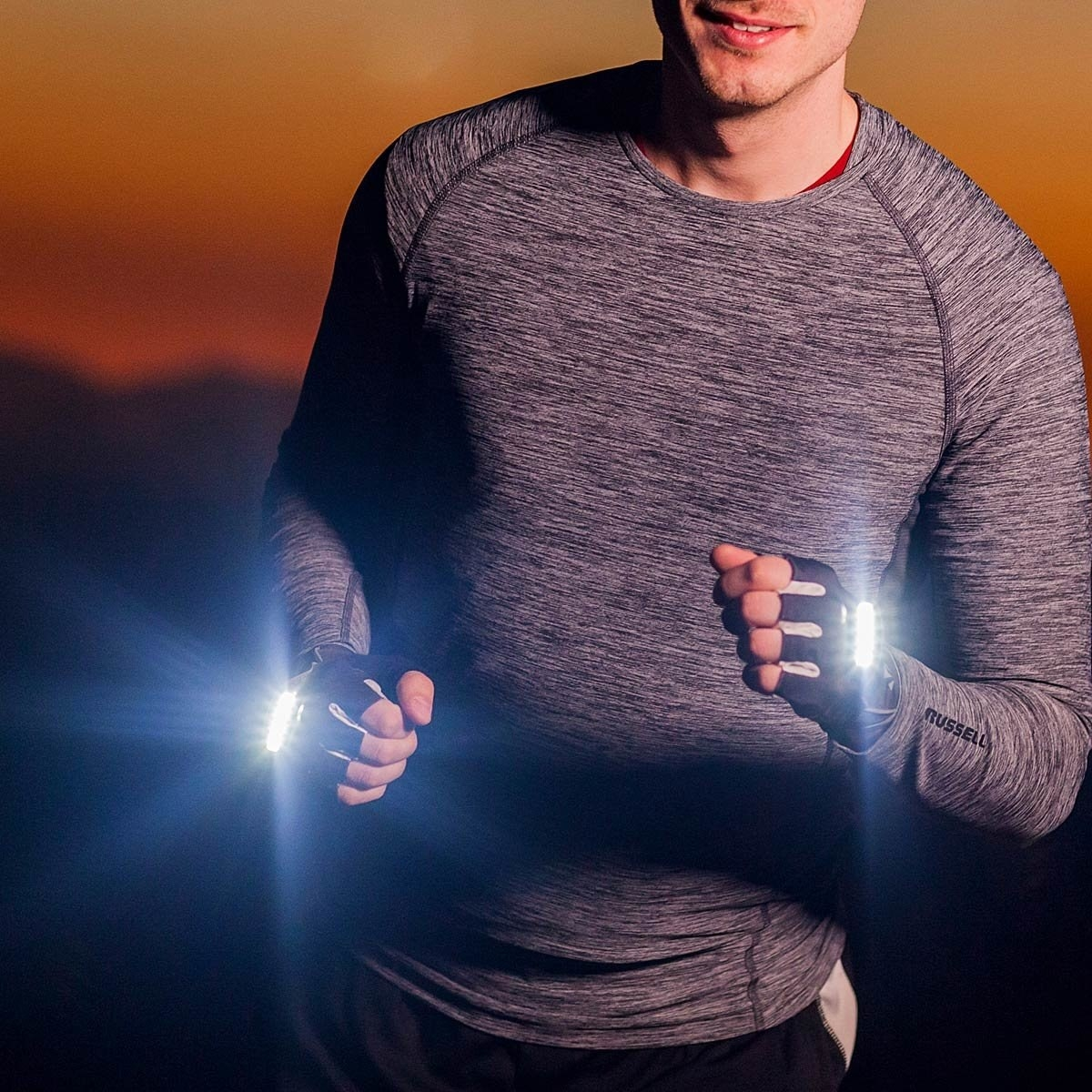 A runner wearing the gloves, which are glowing brightly