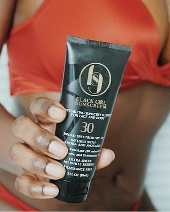 a model holding up a black squeeze bottle of SPF 30 sunscreen