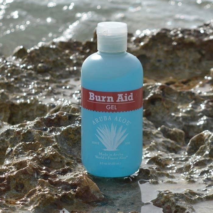 a blue bottle of burn aid gel sitting on beachy rocks