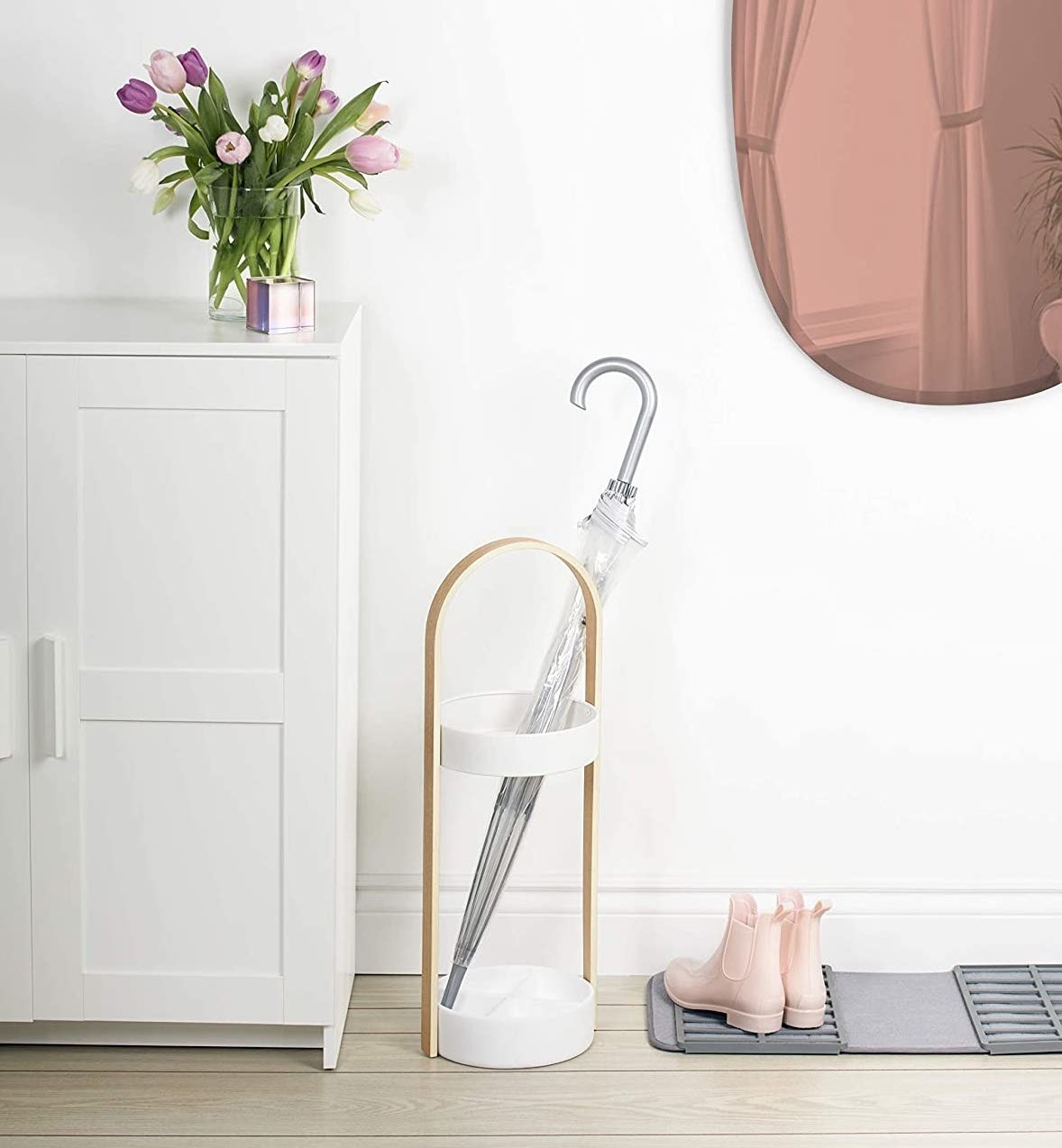 The umbrella stand in a neatly arranged entryway with a clear umbrella inside