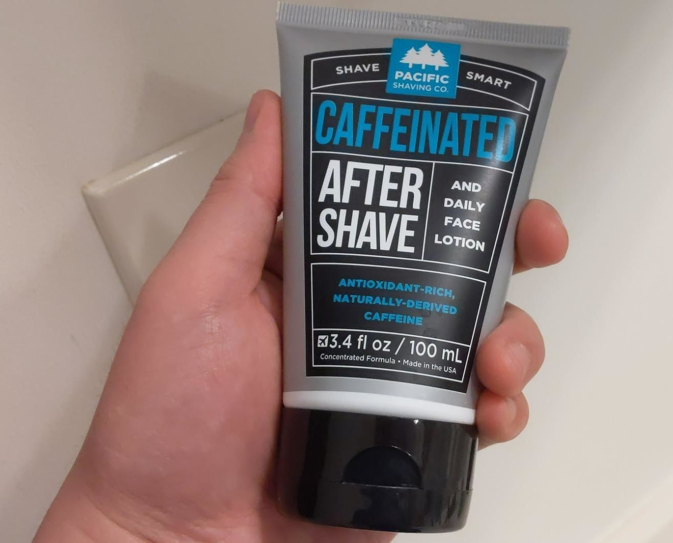 A reviewer's hand holding a grey tube of aftershave with white and blue writing and a black top