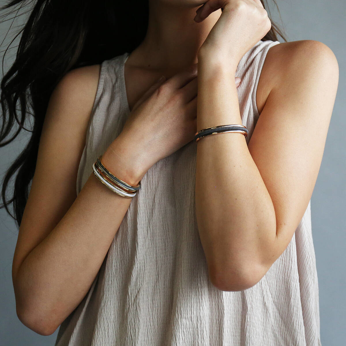 A model wearing the bracelets stacked together