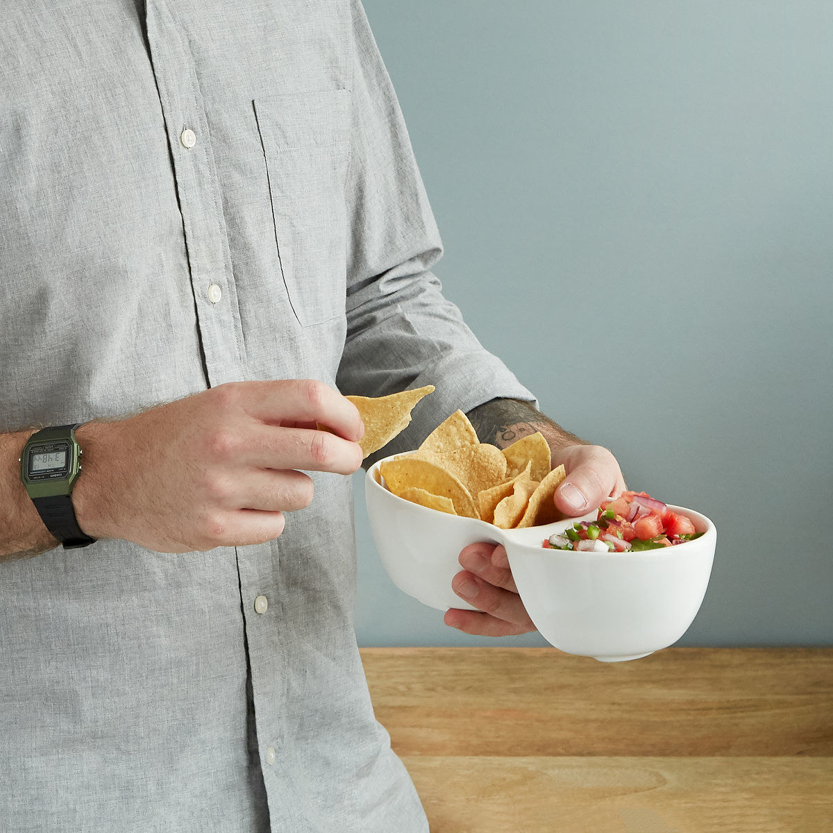 A person using the bowl for chips and salsa