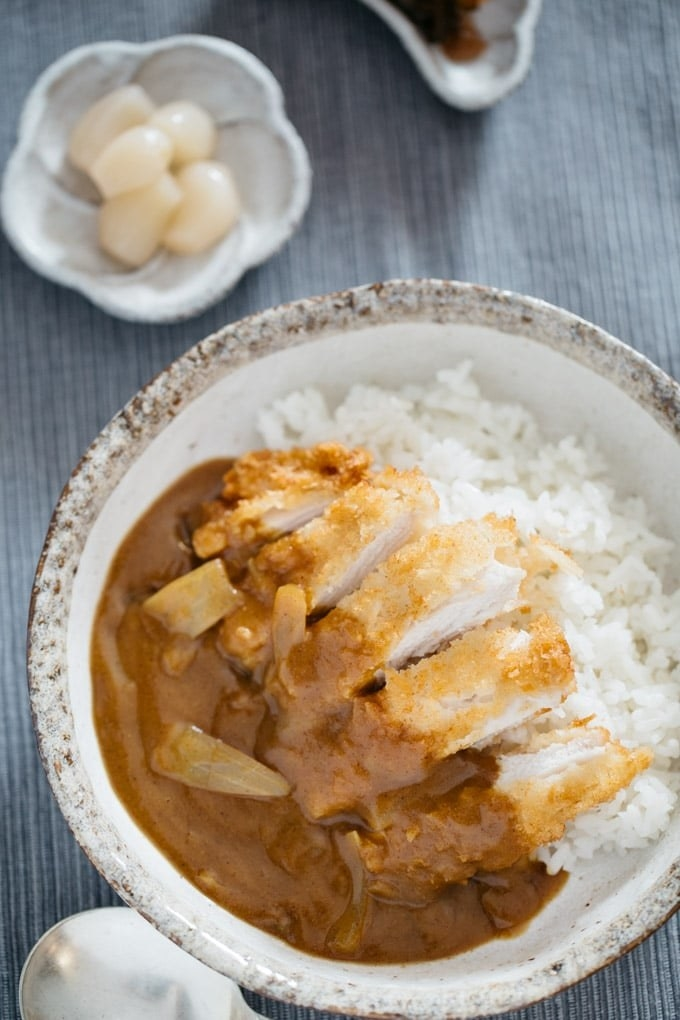 A bowl of fried Japanese chicken katsu over rice with curry sauce.