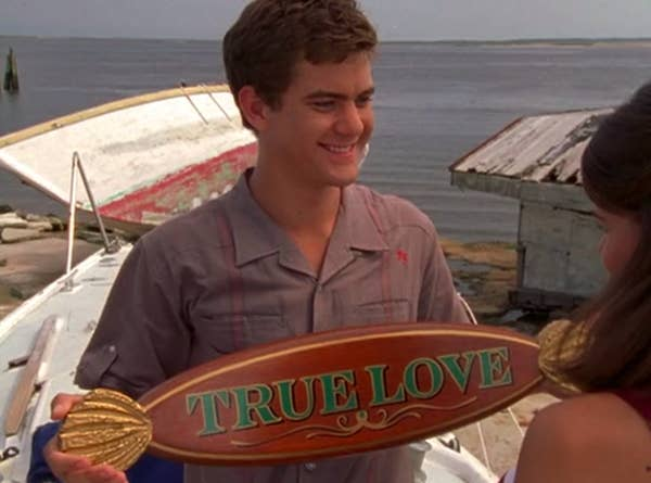 """Pacey holds the """"True Love"""" sign for his boat."""
