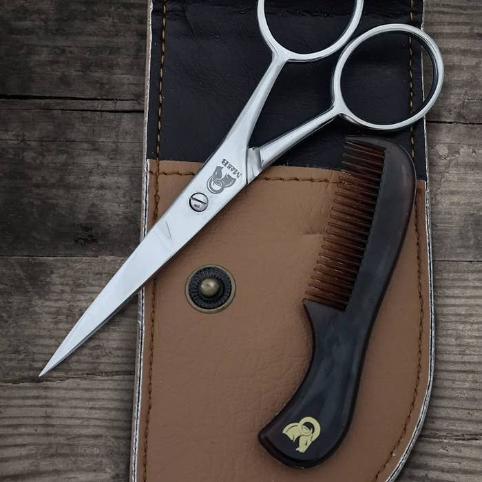 A small pair of pointy metal scissors with a smaller plastic comb atop a light brown leather pouch