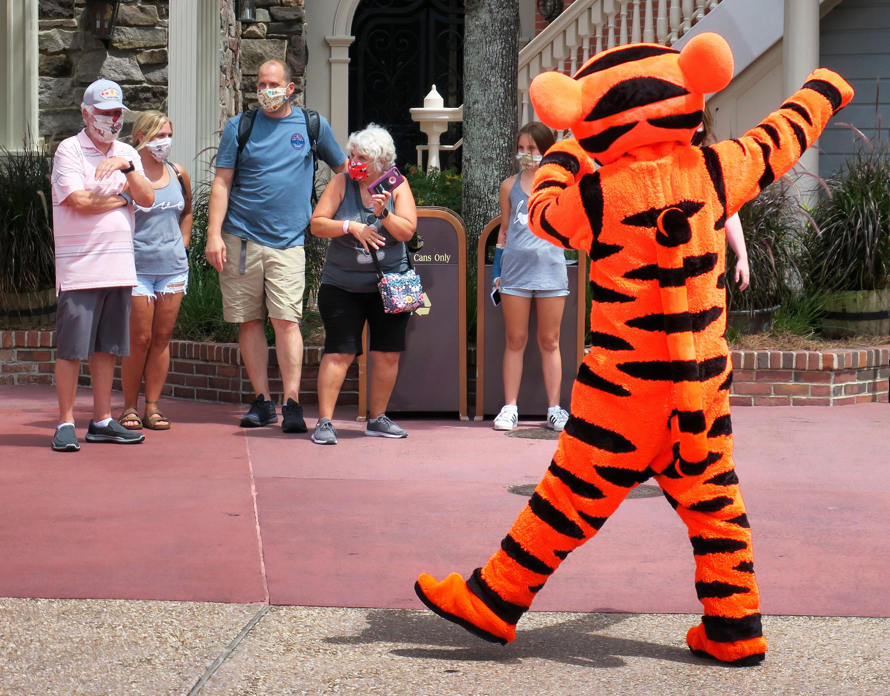 A family wearing masks watches Tigger walk by