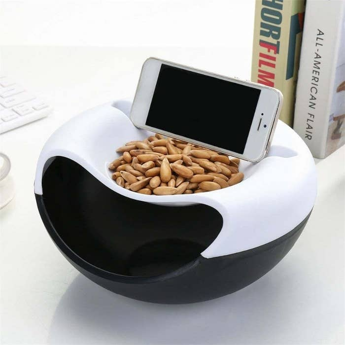 A bowl with nuts inside it and a phone on a built in phone mount