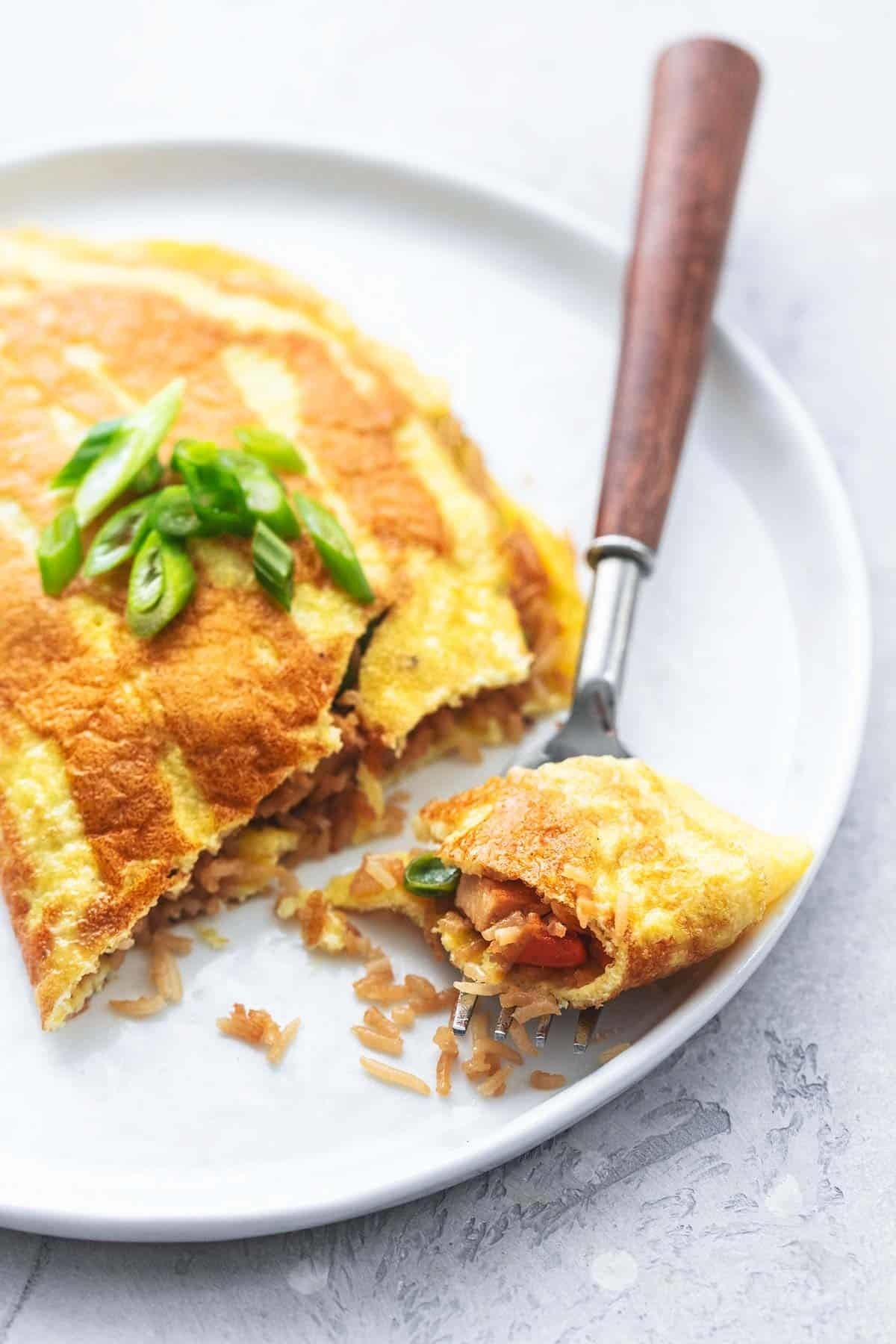 A fork cutting a folded Japanese omelet filled with rice, chicken, and vegetables.