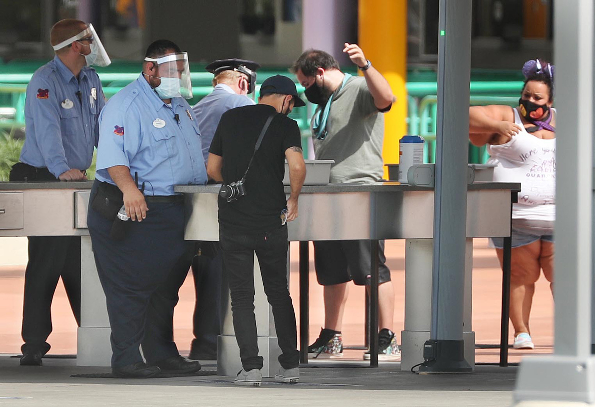 Security guards in face shield check visitors' bags