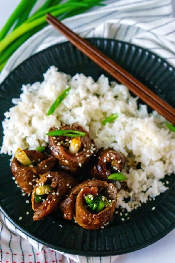 Four beef and scallion roll ups on a plate with rice and sesame seeds.