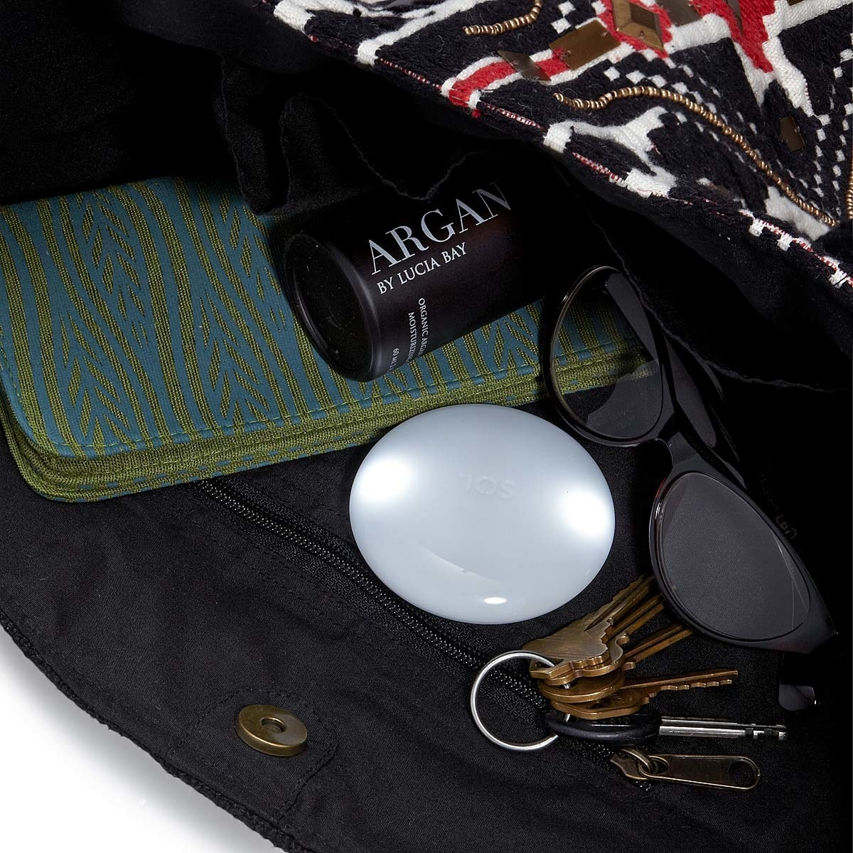 The round light in a purse, approximately the size of a makeup compact
