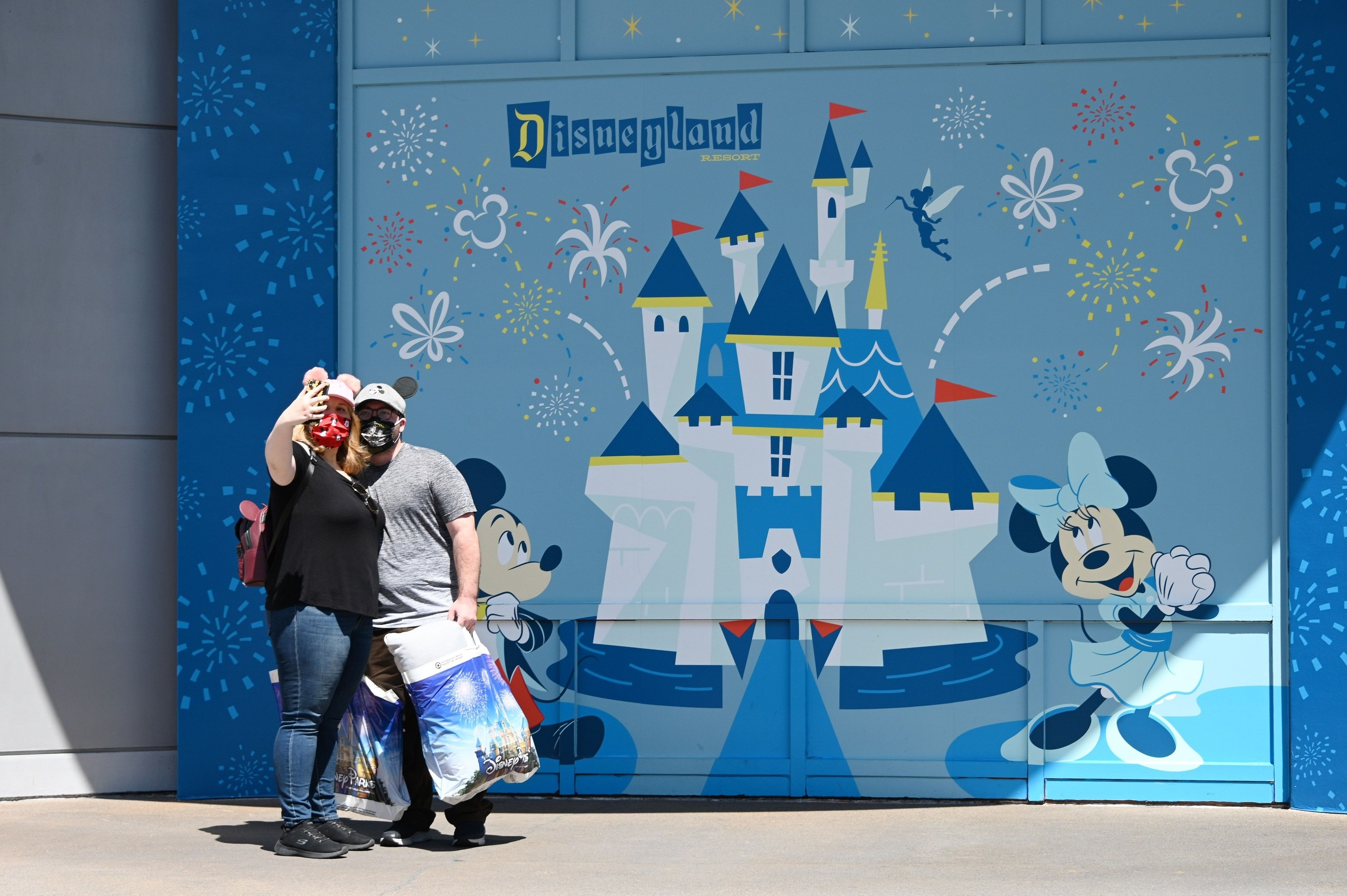 Two people take a selfie in front of a Disneyland mural