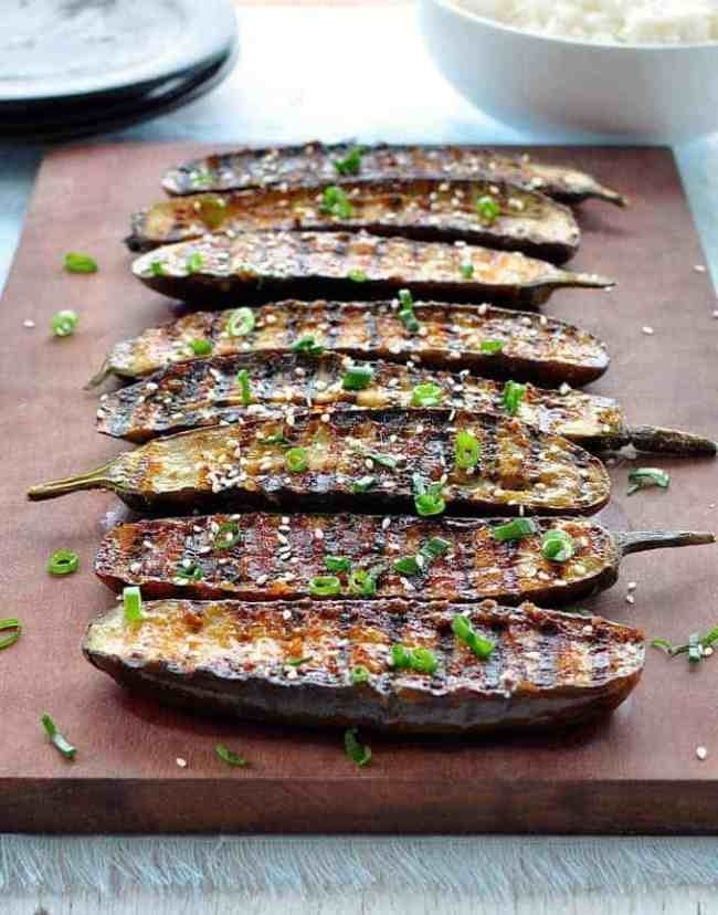 A cutting board topped with slices of miso glazed eggplant .