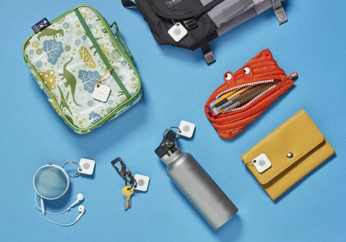 Tiles attached to various items such as a water bottle, wallet, headphones, and a backpack