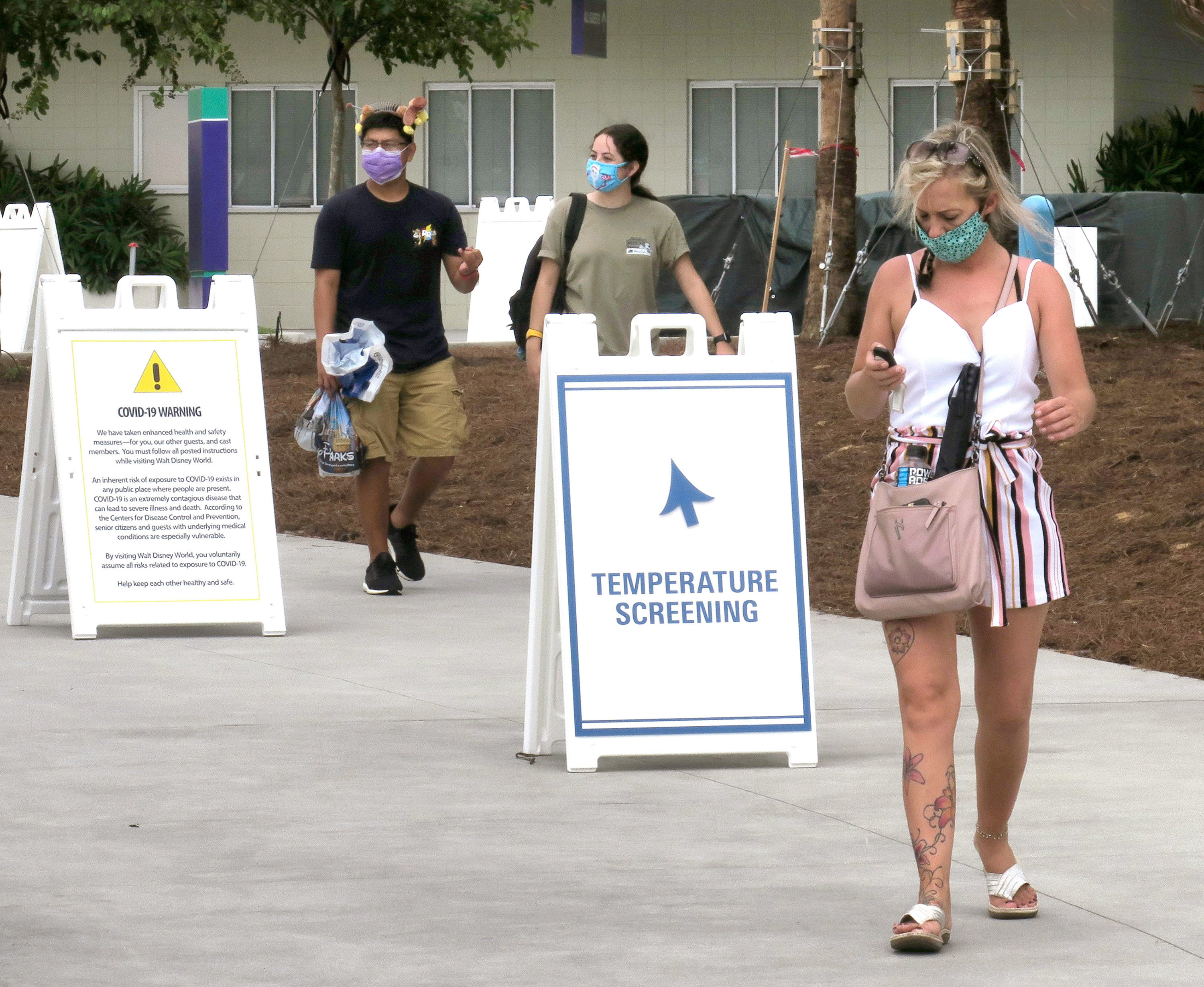 Guests pass signs that point to temperature screening stations and issue COVID-19 warnings
