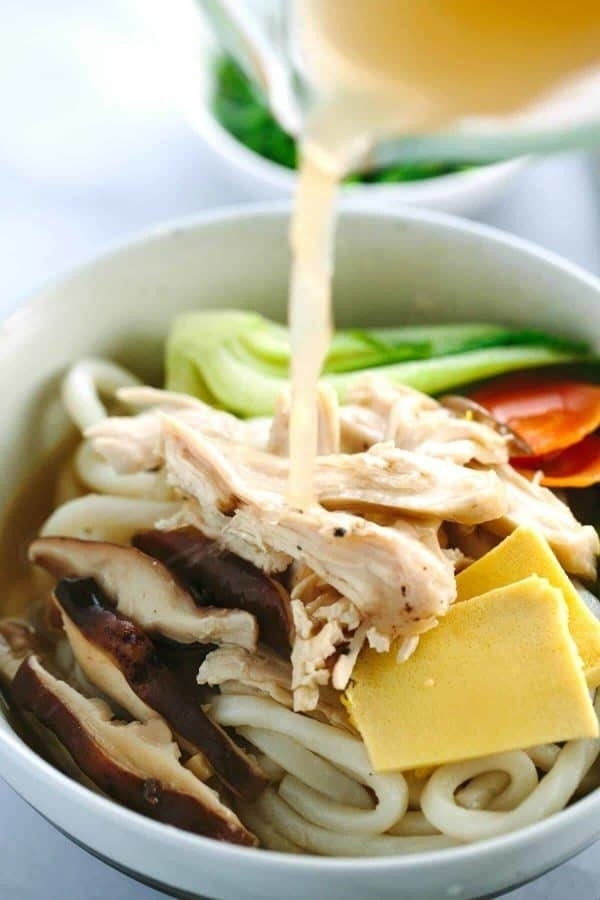 A bowl of udon noodle soup with chicken, peeled ginger, bok choy, and carrots.