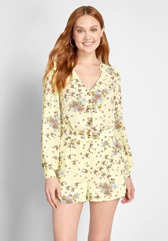A model wearing the pale yellow romper that's also printed with flowers and has a button front