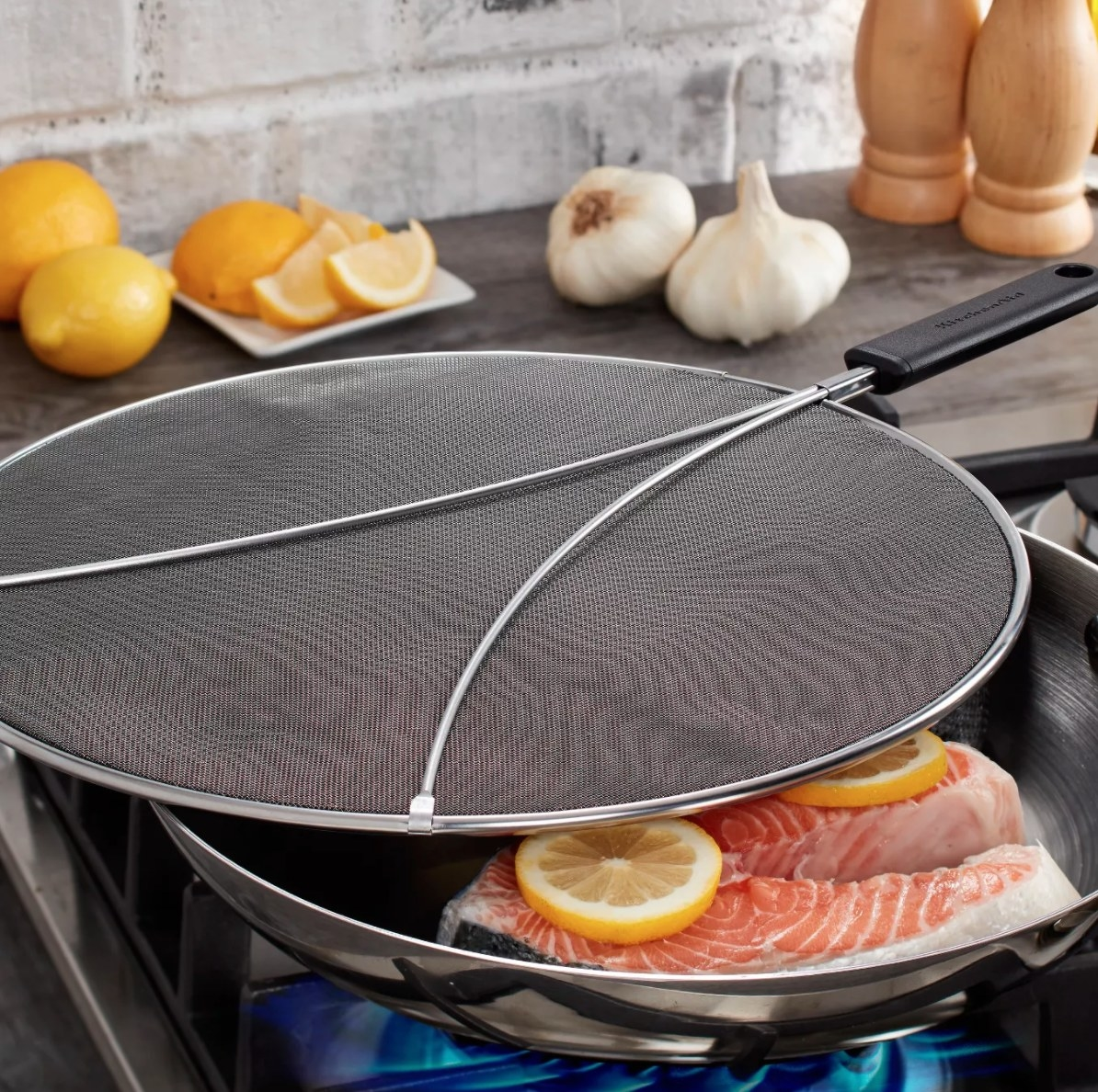 The splatter screen being used to cover a pan that's cooking meat
