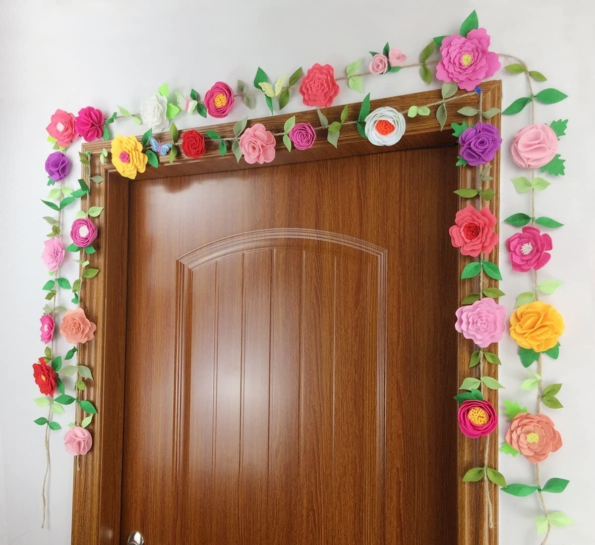 A floral garland made of twine with felted flowers of varying colors and shapes and felted leaves. They are hanging over a doorway.