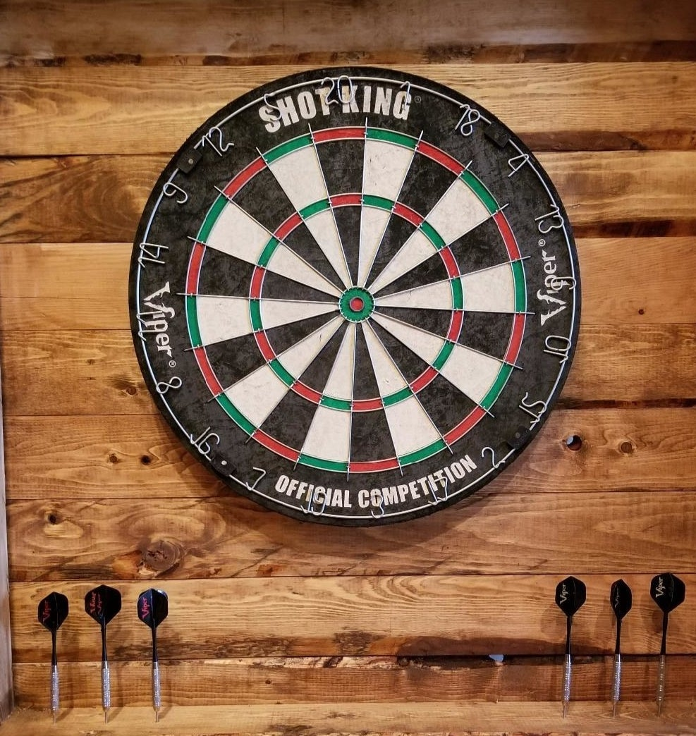 A dartboard with alternating black/white and red/green circular designs and six darts