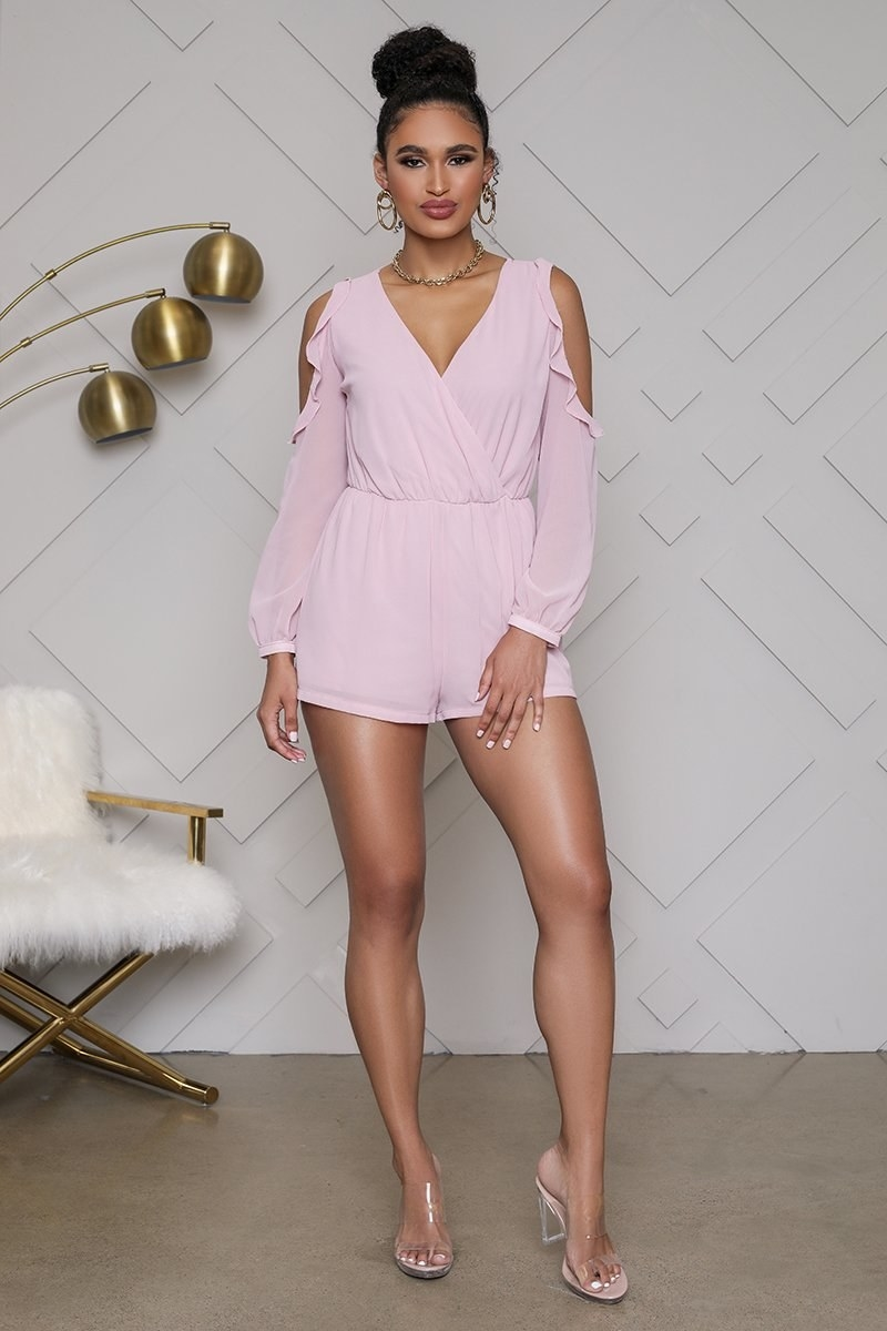 A model wearing the ruffled, long-sleeved, pale purple-y pink romper