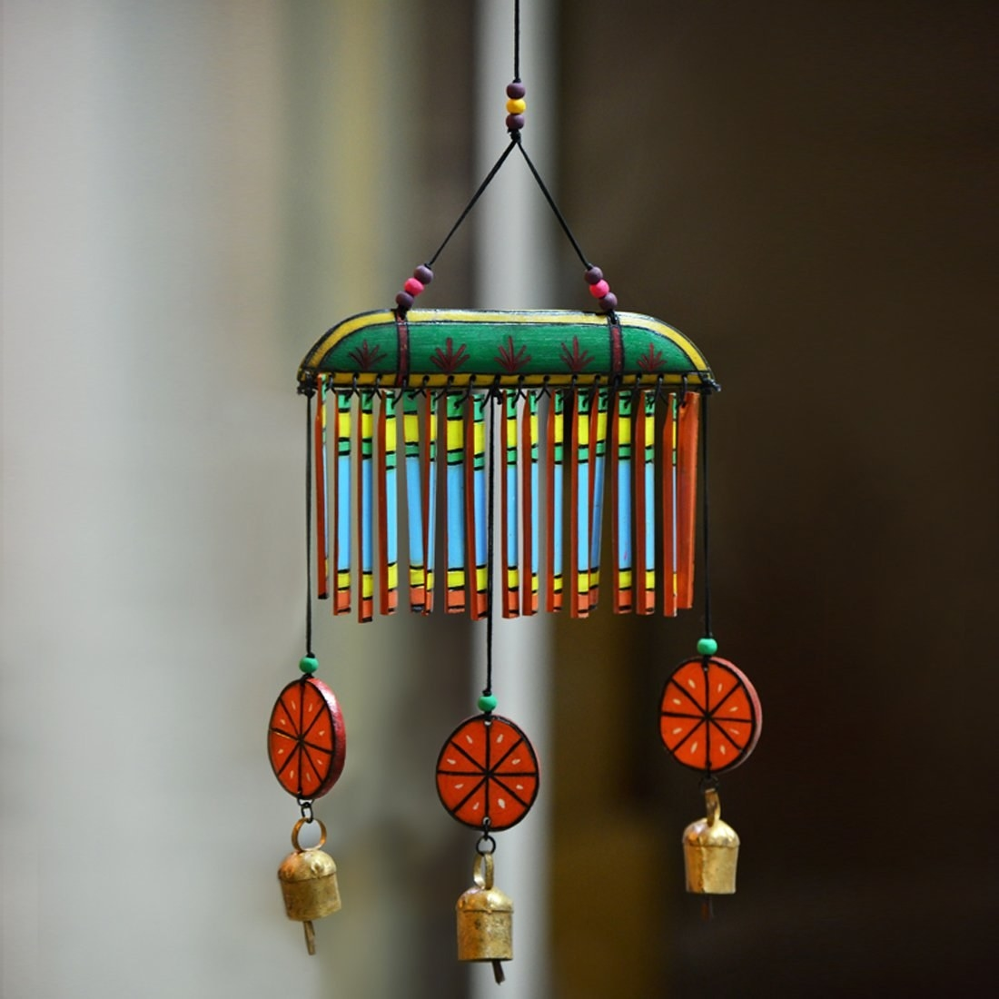 Wooden wind chimes painted in blue, green, yellow and orange. The ends have wooden orange slices and bells hanging on them.
