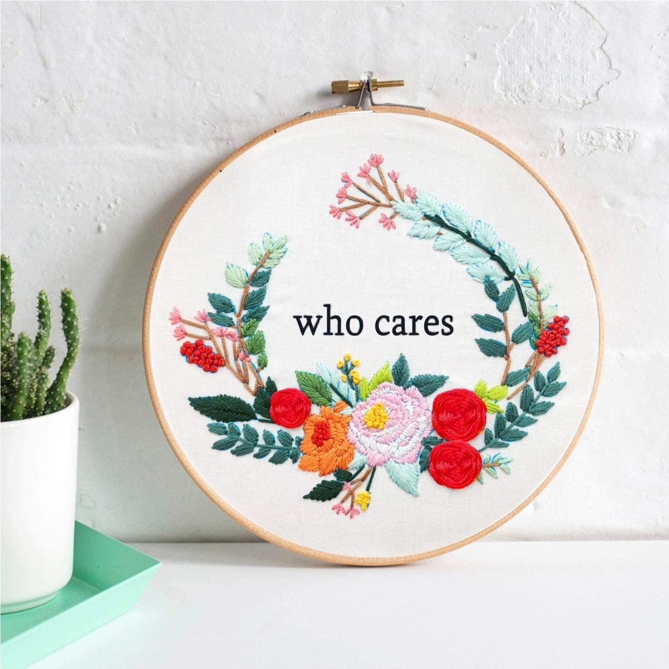 "An embroidery hoop with a finished piece that has flowers around the words ""who cares"""