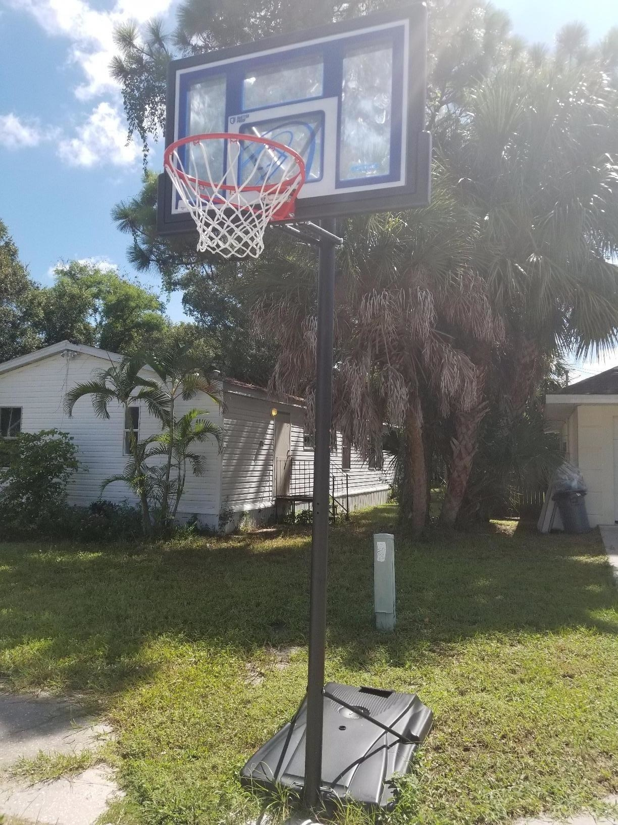 An outdoor basketball hoop with black base and pole, red rim with white netting, and clear blackboard with blue and black accents
