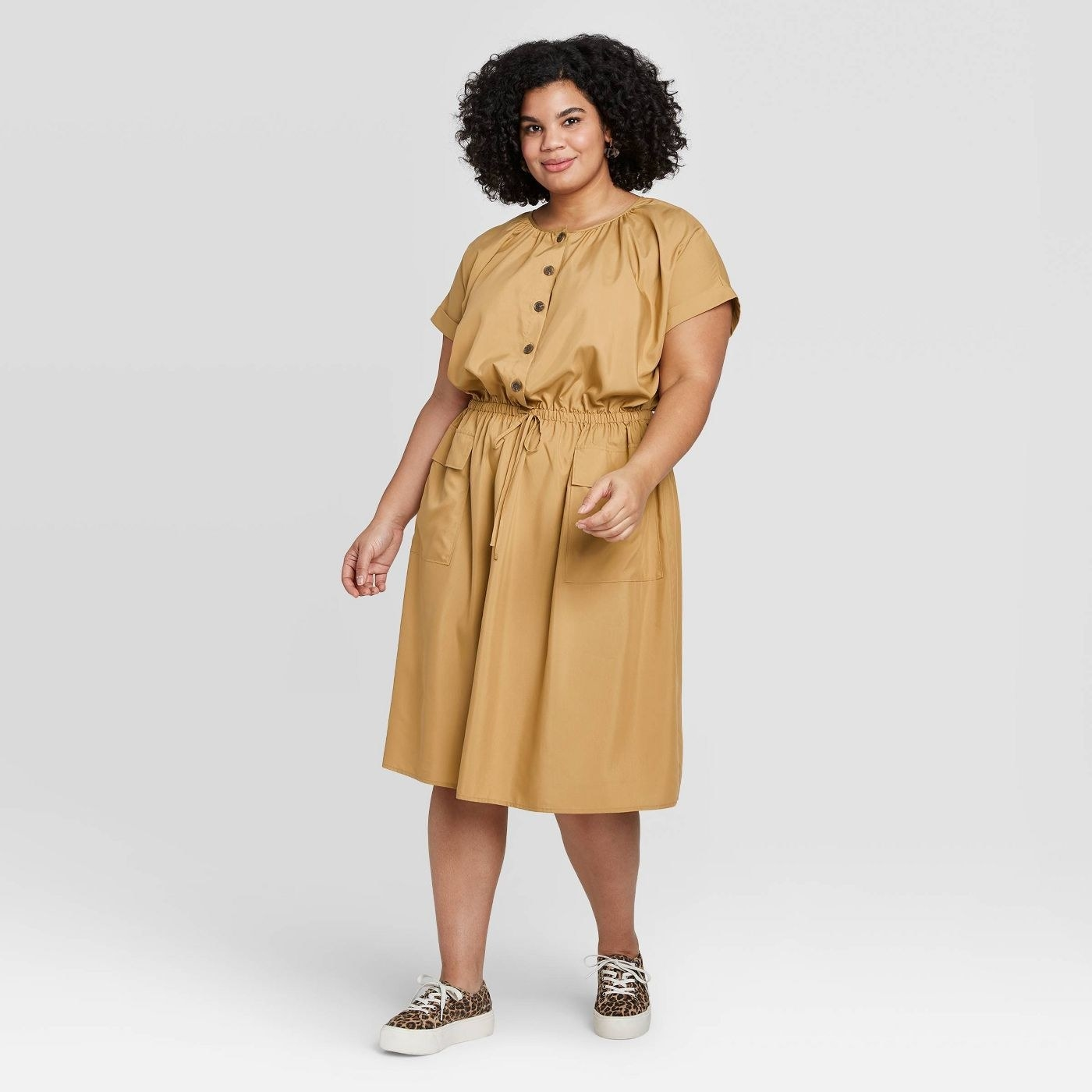 model wearing short sleeve midi dress with button detailing and tie waist