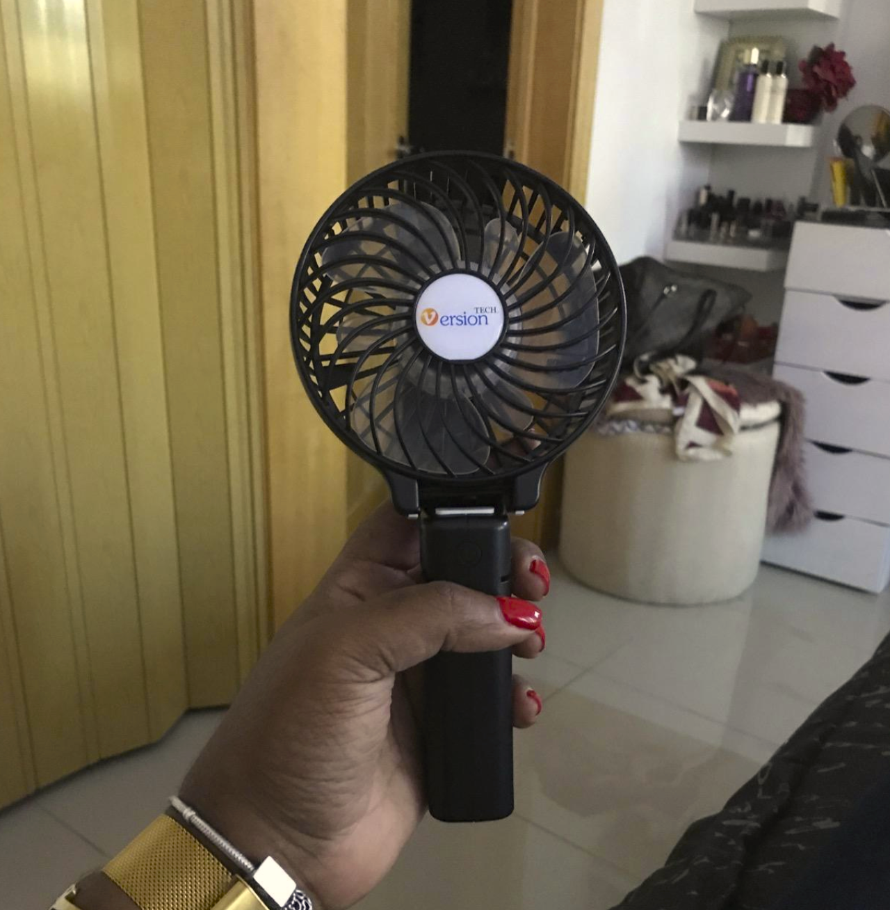 reviewer's hand holding the fan which is circular on the fan end has a handle