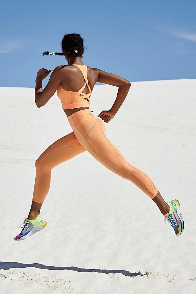 Model running in sand wearing the leggings in orange
